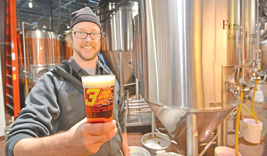 Carolina Brewery brewmaster Nate Williams holds a glass of 'Copperline' beer, which won a Silver Medal at competition in Colorado.