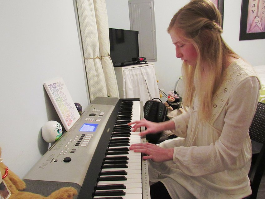 Abigail Holmes, 14, says she taught herself the piano as part of coping with anxiety and depression. Here, she's playing a version of a song by the music artist Panic at the Disco.