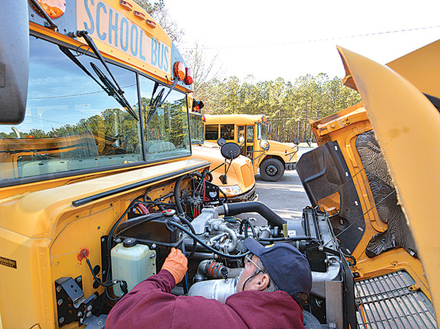 School transportation employee Eugene Dowdy checks the antifreeze solution on a bus at Moncure School last week. With the winter upon us, it's not too late to get your vehicles winterized.