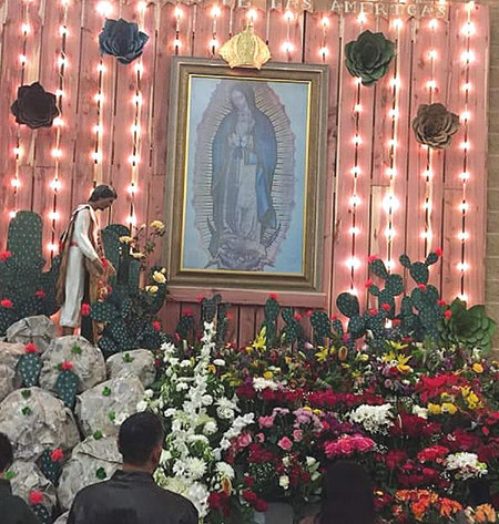 Flowers surround the painting of Our Lady of Guadalupe at St. Julia Catholic Church.