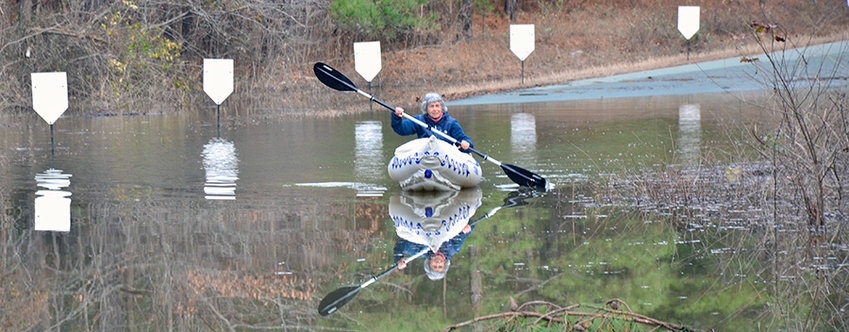 Jeremiah Drive resident Maja Kricker uses a kayak to get her car after flooding stranded families.