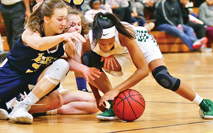 Lady Charger Rae Mcclarty, right, tries to control a loose ball against Lee Senior in the first round of the Christmas Invitational in Sanford last week. NW won the game, then won again on Friday to make it to the finals where the locals lost to 4A power Raleigh Millbrook.
