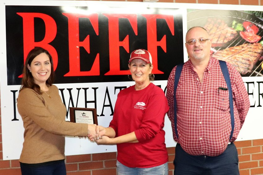Ashley Herring (left) of the N.C. Cattlemen's Beef Council hands the Beef Backer award to Carolina Stockyards Restaurants co-owners, Sherry Duncan and Robert Crabb.