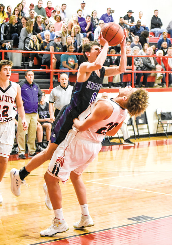 Chatham Central's Hayden Nall (bottom) draws a charge from Chatham Charter's Cole Milholen on Tuesday night in Bear Creek. Chatham Central captured the crucial 1A Central Tar Heel Confernce game 66-64 in a triple overtime thriller.