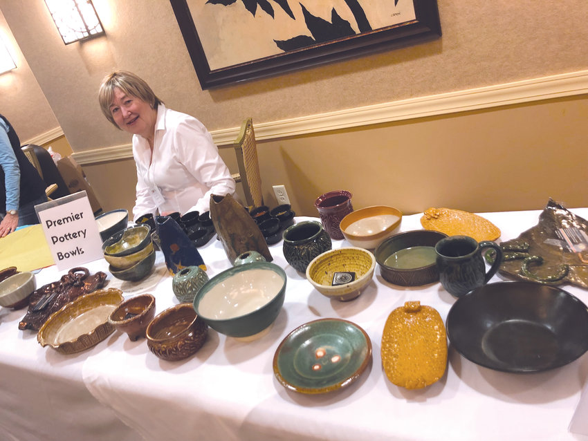 Volunteer Jackie Durham mans the 'Premier Pottery Bowls' booth for those with a premium ticketat CORA's Empty Bowls event.