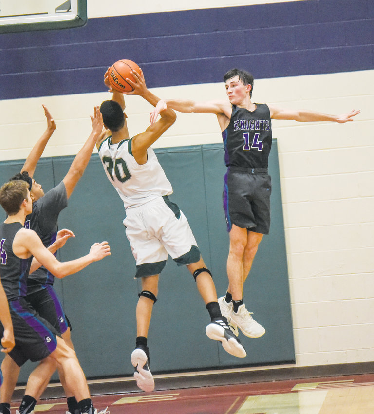 Chatham Charter's Connor Murphy (14) goes up for a block attempt against Resarch Triangle's Keeyan Itejere (30) in CTH tournament championship action last Friday night in Altamahaw. Research Triangle won the nailbiter 46-45.