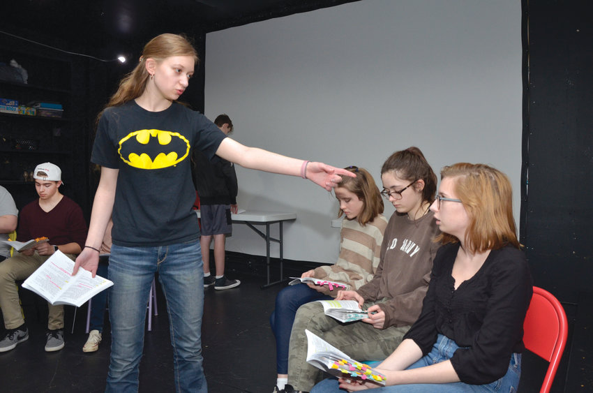 The character of 'Freak/Eric,' played by Jacquie Anthenian in the play 'Columbinus,' holds a gun on frightened classmates in the high school library at Columbine High School. Behind Anthenian, Ethan Galiger, Jake Dusenberry, Alayna McLandsborough, Hannah Conners and India Nykamp portay students under fire during the massacre. The students  rehearsed the play at the Sweet Bee Theatre, where the performance is planned for April 19-20. The actual event occured April 20, 1999.