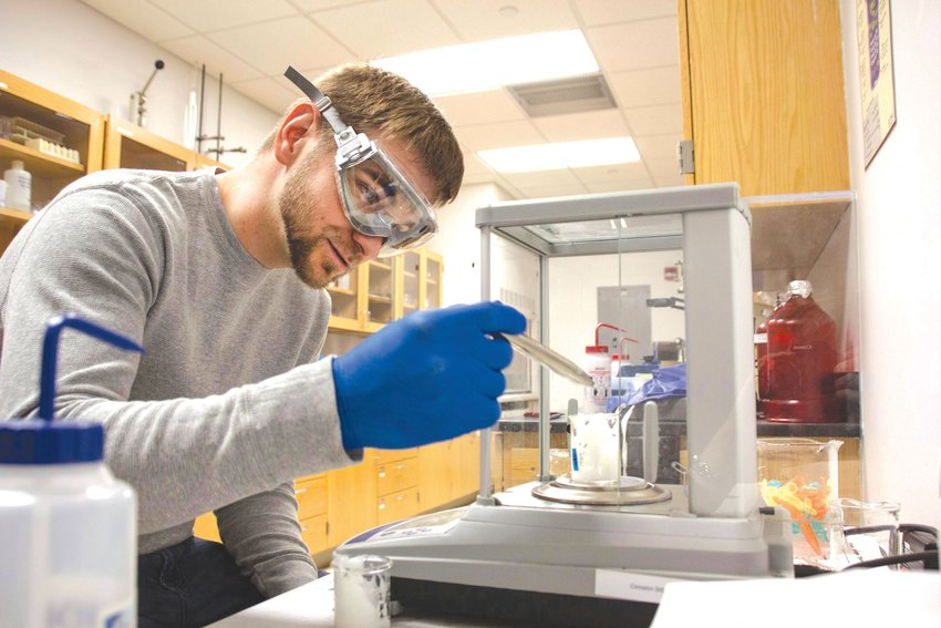 Frostburg State University senior engineering major Brent Patterson processes nanocellulose suspended in liquid as part of the process of studying ways to create a very strong, plant-based product with the goal of creating new bullet-resistant materials.