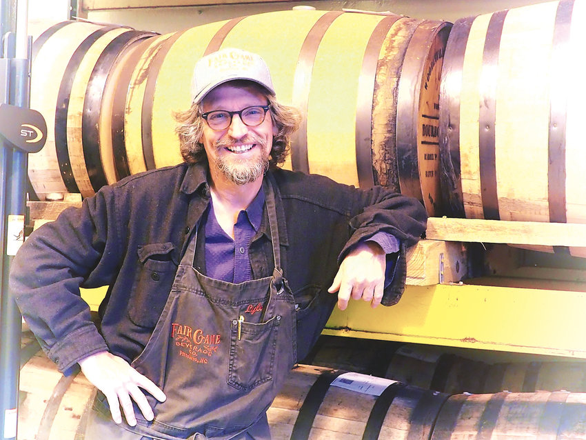 Fair Game's Lyle Estill stands with barrels where their unique spirits age.