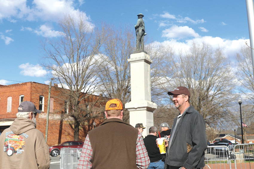 """Chatham County resident Peter Long (holding cup) said Monday that Chatham's Confederate monument didn't become an issue """"before Trump got elected."""" Long was among several residents who gathered around the statue Monday afternoon in advance of a Chatham County Board of Commissioners meeting."""