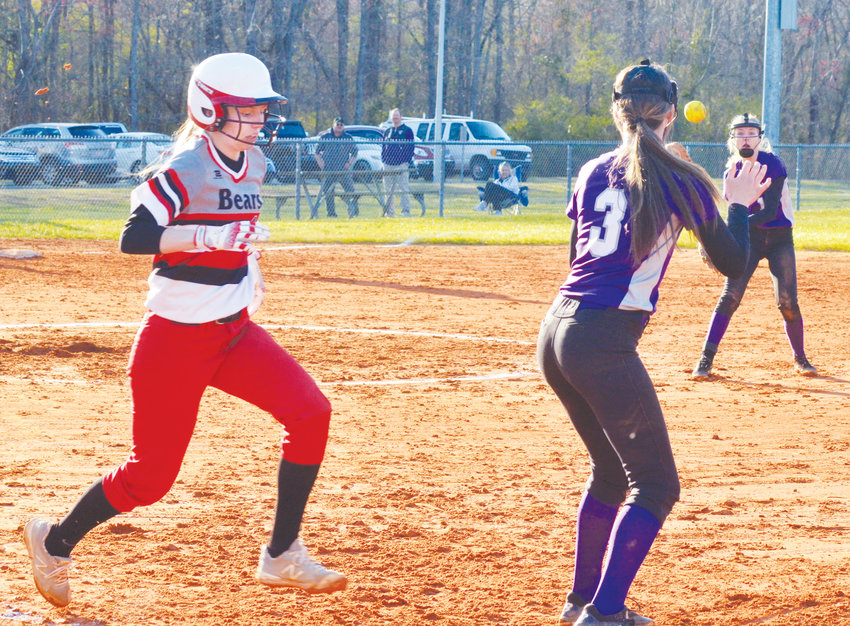Chatham Central's Madelyn Elkins races for first base to beat the tag as Chatham Charter's Taylor Poe waits for the ball thrown by Sydney Bowman.