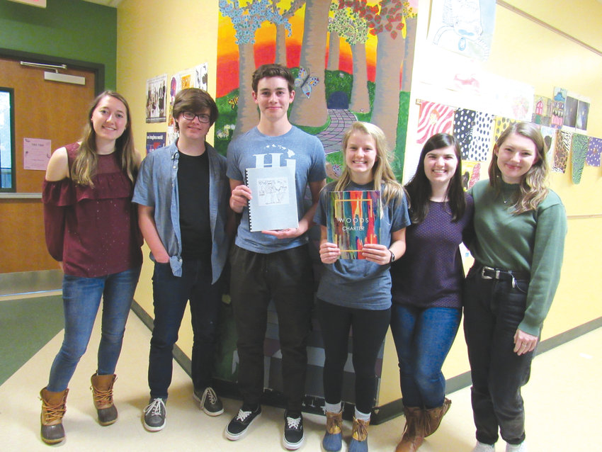 Members of the Woods Charter yearbook staff hold the 2003-2004 and 2017-2018 editions of the volume. Pictured are, left to right, senior Alex Christian, sophomore Carson Cole, sophomore Eli Terrell, senior Cheynie Wray, senior Emily Tracy and senior Birdie Romatzick.