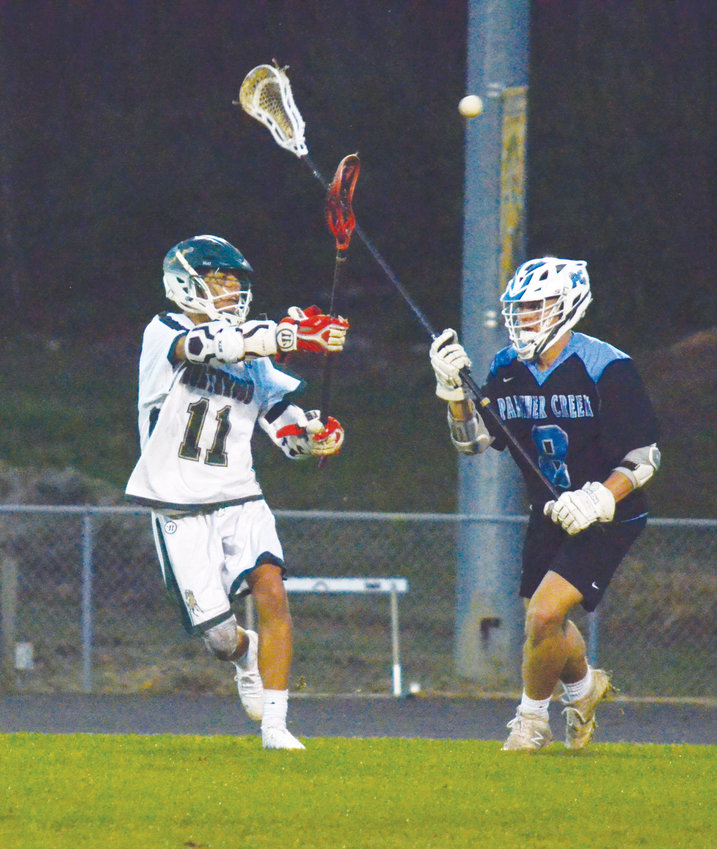 Northwood's Dacota Egnaczak passes the ball past Panther Creek's Fabian Almodovar at the Northwood Athletic Complex April 10. Northwood dominated the opposition with a lopsided score of 20-7.