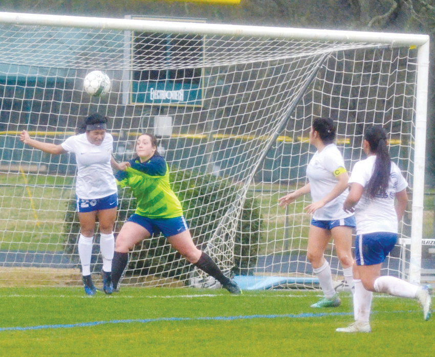 Jordan-Matthews' Janet Solano does a header in recent High School action. Goalie Hannah Jones is ready to make the play as teammates Brisa Romero and Iris Grandos stand by.