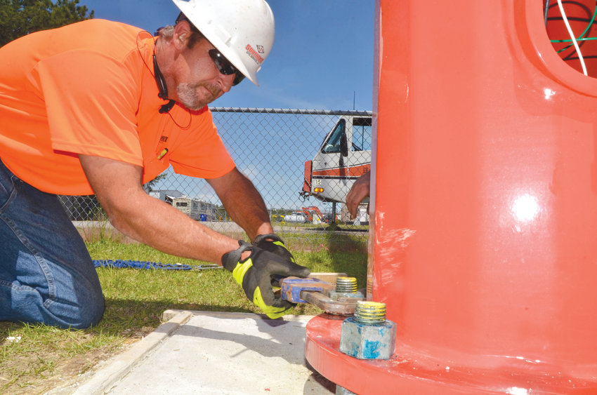 Jason Davis tightens one of the bolts on the new lighting beacon at Siler City's airport Wednesday. The new tower light will be able to be seen over two miles, with a cleaner, clearer light than was used before.