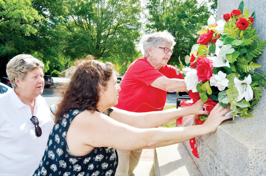Jane Hinnant, secretary of the Winnie Davis chapter of the United Daughters of the Confederacy in Pittsboro, watches as the annual wreath is laid onto the Confederate Memorial statue laset Thursday by Historian June Price, and President Barbara Pugh.