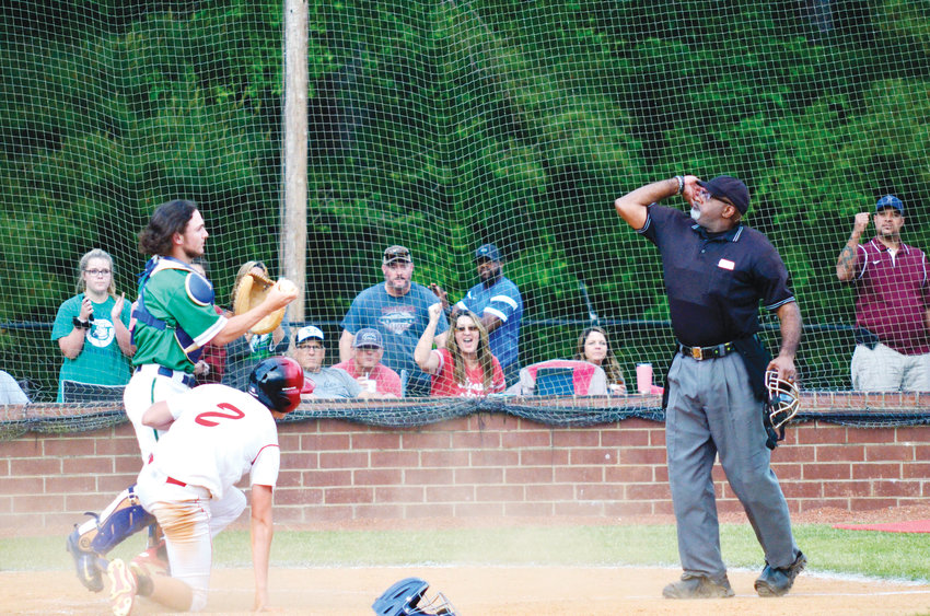 Uwharrie Charter's catcher Colyn Grissom holds up the ball for umpire Doug Greene to make the call. Grissom tagged Chatham Central's base runner Lofton Dodson at the plate for the out.