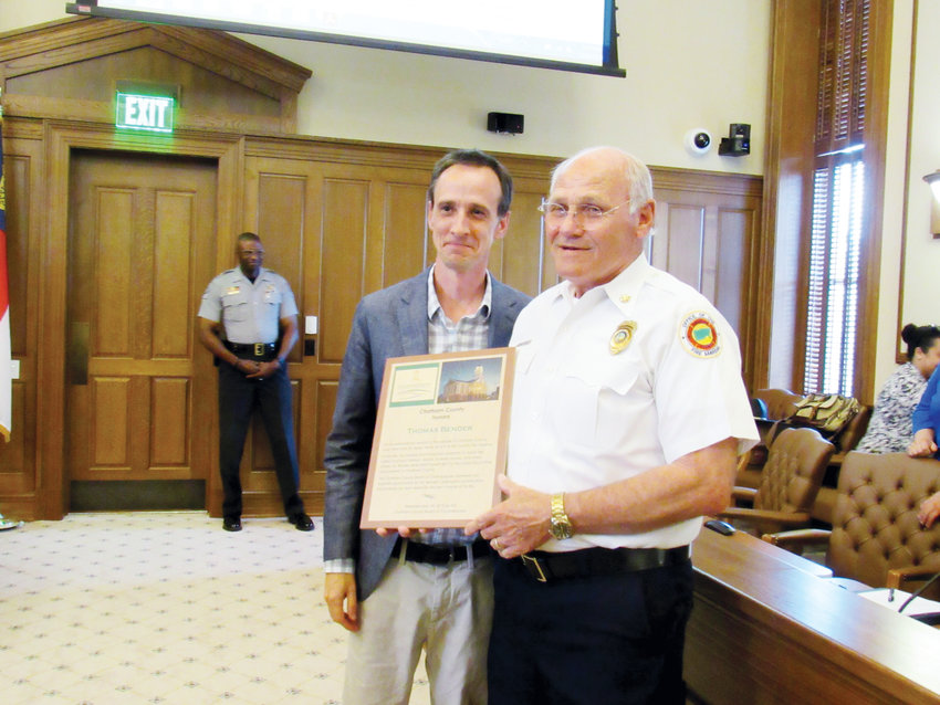 Chatham County Board of Commissioners chair Mike Dasher (left) presents Fire Marshal Thomas Bender with a plaque in honor of his 26 years of service to the county. Bender is retiring May 31.