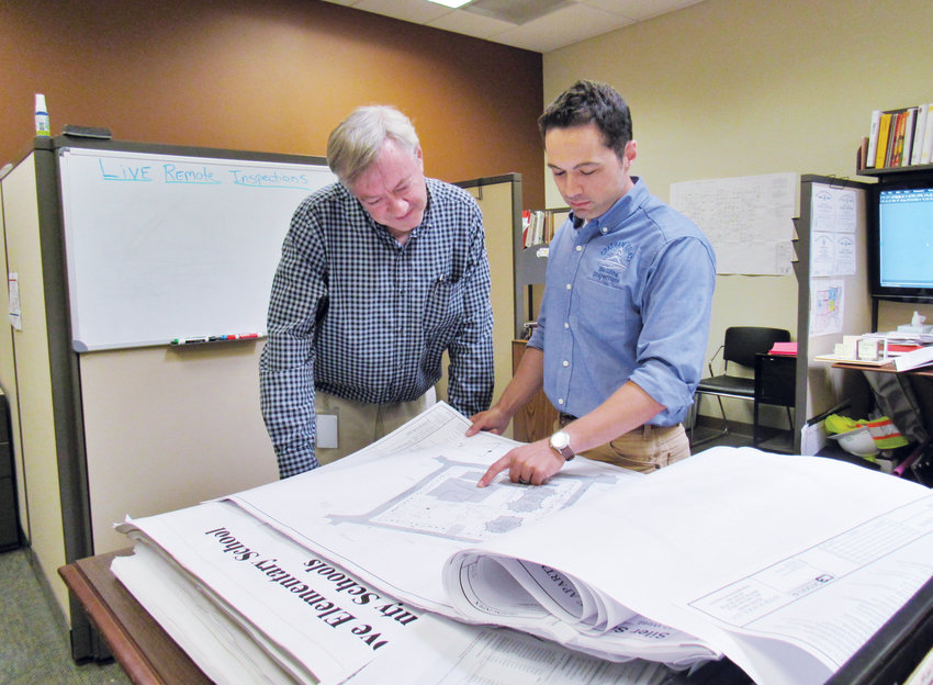 Chatham County Director of Central Permitting and Inspections David Camp, left, looks over plans for an apartment complex with Brandon Ancona, one of the county's inspectors.