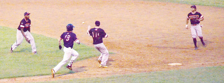 Deep River Muddogs Trevohn Jeffrey makes a toss to his pitcher to get Carolina Coyote Cort Maynard out as Muddog Rafael Ortega backs the play. Maynard was safe in Wednesday's game at Craven Stadium in Ramseur, but the top half of the seventh inning play didn't change the outcome of the game, with the Coyotes losing 2-1.