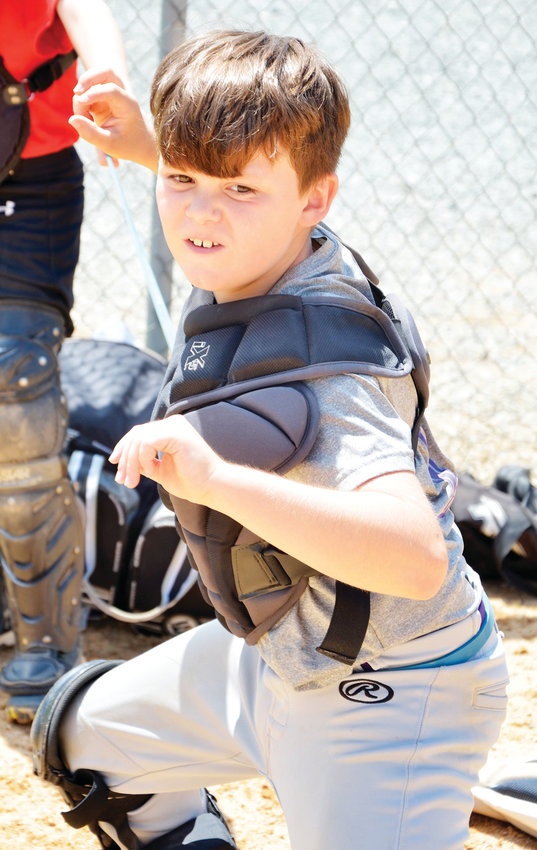 Nolan Shaw, 9, takes part in a strength-building exercise at Benji Johnson's clinic at Bray Park in Siler City. The students had thick bands around their waists to create resistance from their partner as they stood from a squatting position to throw.