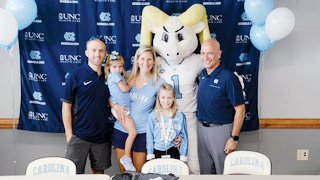 Kelsie Houston of Pittsboro signs with the University of North Carolina women's volleyball program in Carmichael Arena in Chapel Hill on Saturday. Pictured (from left) are father Nathan, sister Mackenzie, mother Kimberly, Kelsie, UNC mascot Ramses and UNC volleyball coach Joe Sagula.