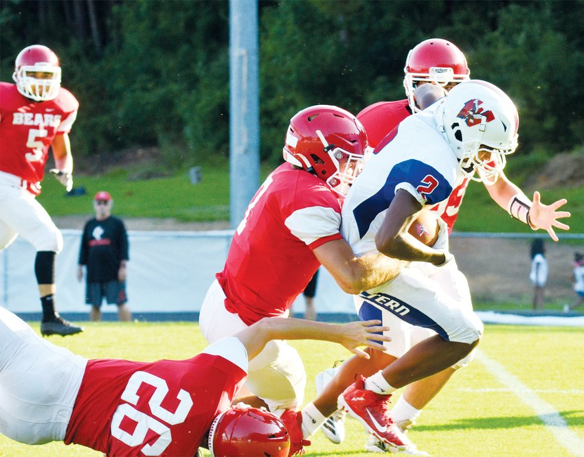 Chatham Central's Collin Lagenor, on the ground, and William Douglas take down Western Harnett's Misha'el Vines in early scrimmage play last Friday.