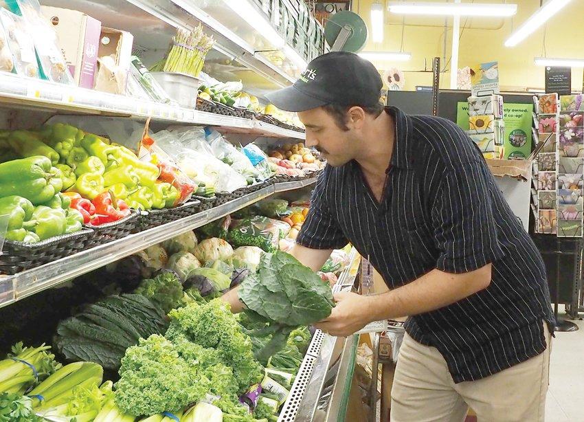 Evan Diamond restocks the shelves at Chatham Marketplace.