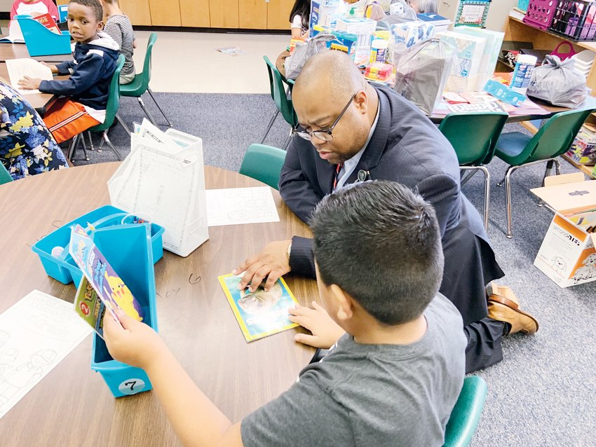 Chatham County Schools Superintendent Derrick Jordan helps a student Monday morning in a first-grade classroom at Siler City Elementary with a book reading assignment.