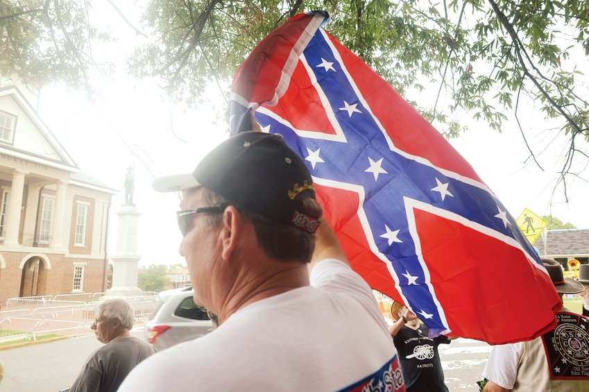 Tommy Carroll held a Confederate battle flag at a rally earlier this month in downtown Pittsboro.