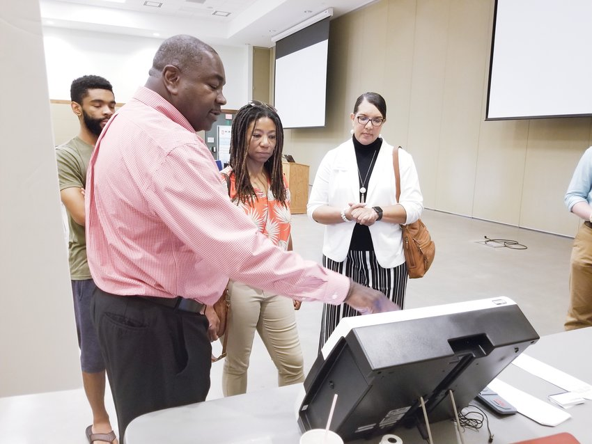 Chatham County Board of Elections Director Pandora Paschal, Chatham County Commissioner Karen Howard and her son receive a demonstration from a representative of ES&S two weeks ago during a public demonstration of election equipment.