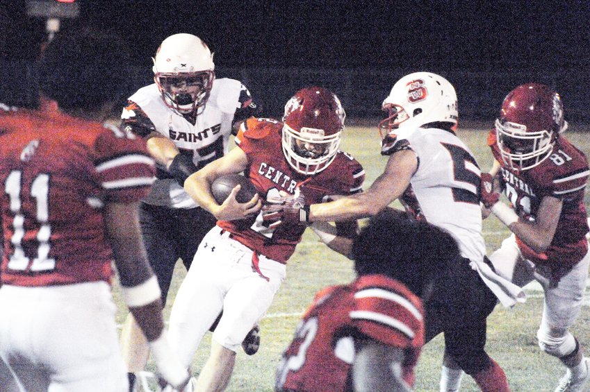 Chatham Central's Tyler Oldham takes a handoff and scrambles for yardage against the North Wake Saints defensive lineman Jackson White last Friday.