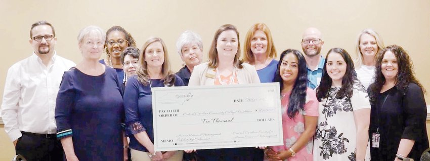 Dr. Emily Hare (holding check), Executive Director of Central Carolina Community College (CCCC) Foundation, visits with Central Carolina Society for Human Resource Management (CCSHRM) members. CCSHRM has sponsored an endowment to create a legacy scholarship at CCCC.