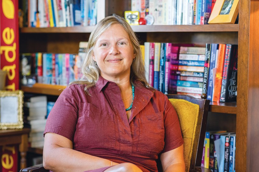Appropriately surrounded by shelves filled with books, Dolly Sickles is an author and book reviewer.