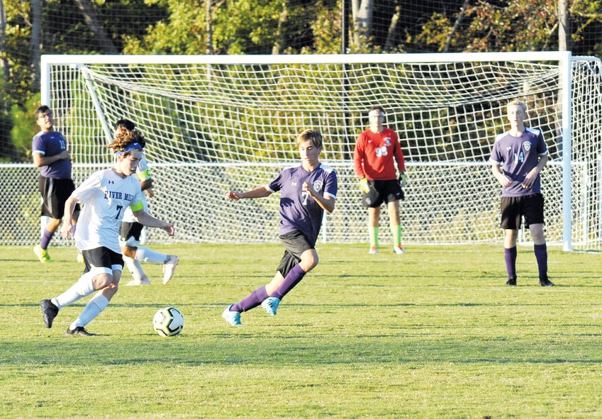 River Mill Academy's Kaleb Risen manuevers around Chatham Charter's Cameron Turner to shoot for points in last Monday's match in Siler City. The Jaguars were held scoreless by the Knights in a 2-0 victory on Charter's new soccer field.