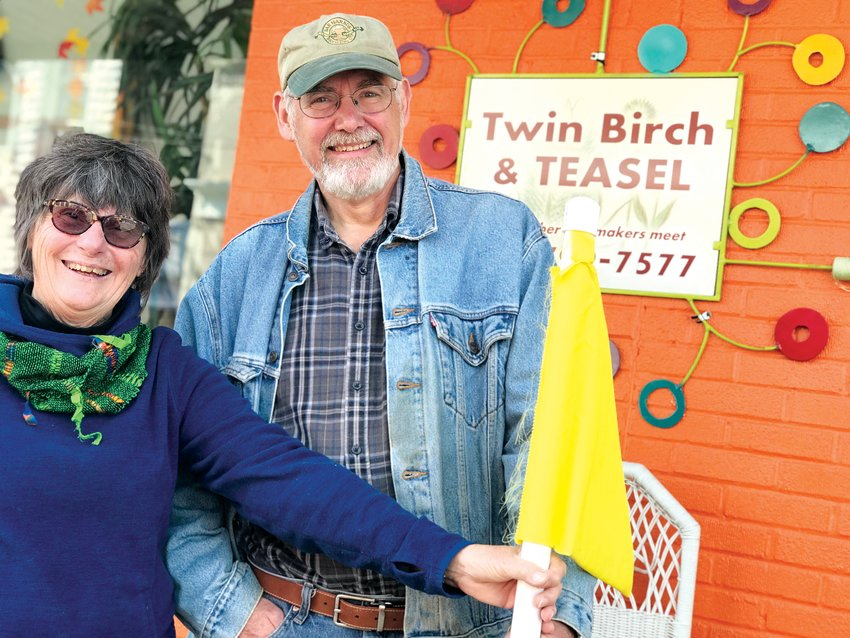 Sue and Rich Szary pose in front of Twin Birch & Teasel, their business on N. Chatham Avenue in Siler City. When open, Twin Birch is one of a number of downtown businesses flying yellow flags.