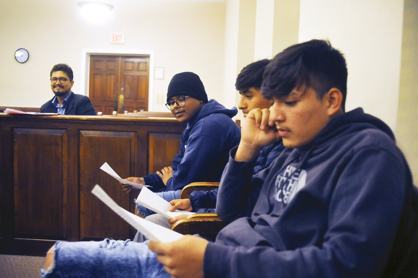 Pablo Avendano, program manager for teen court, works with the Teen Court jurors (pictured here in 2019) Chris Valdivia, Miguel Becquer-Ramos, and Enrique Dimas, (left to right) as they listen and study the facts in the practice case before them. The event, in the courtroom at Siler City's Town Hall Nov. 13,  2019 covered all aspects of a real trial, with the jury making the final decision regarding the punishment for the crime committed by the accused.