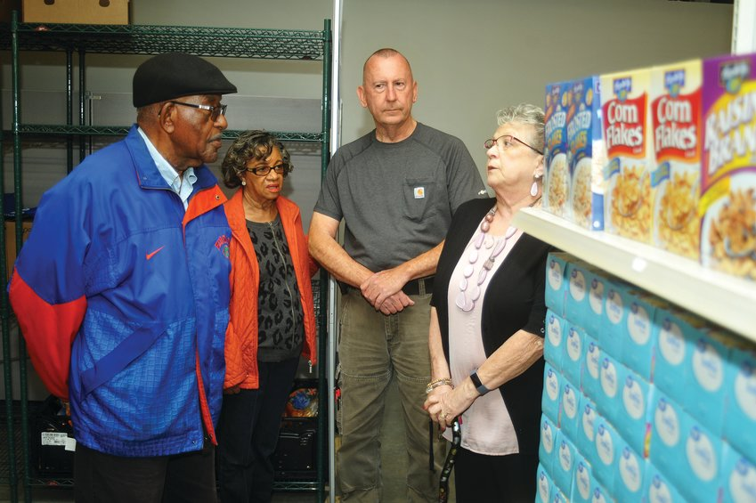 Graphel Paige, his wife Ella and Siler City Commissioner Curtis Brown listen to Diane Smith, West Chatham Food Pantry's executive director, talk about the organization's new offices at Chatham Trades in Siler City.