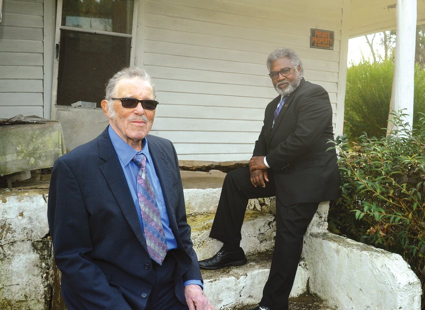 Carl Bryant (left) and Rev. Ricky R. McKinney Sr. relax on the front steps of Carl's old home on Gade Bryant Road in Moncure, where he and his siblings were raised. Carl is the last surviving member of the Bryant family.