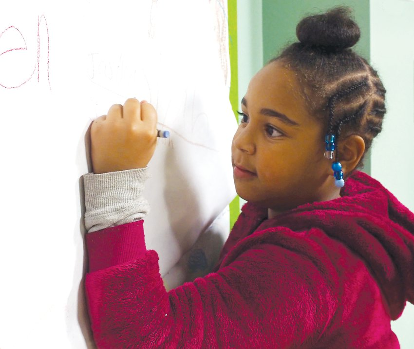 After eating, many of the children at the Siler City Community Meal took the opportunity to color on a large paper canvass hung for artists in the making.