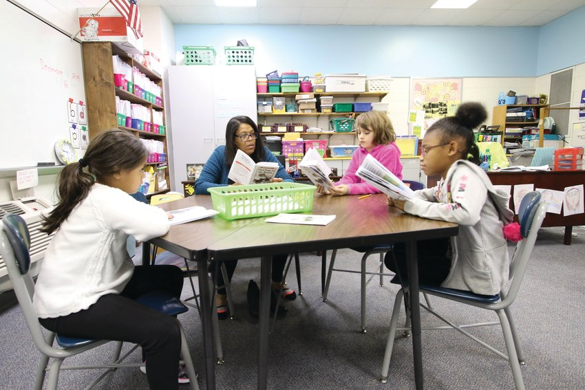 Cotton reads with a small group of her students.