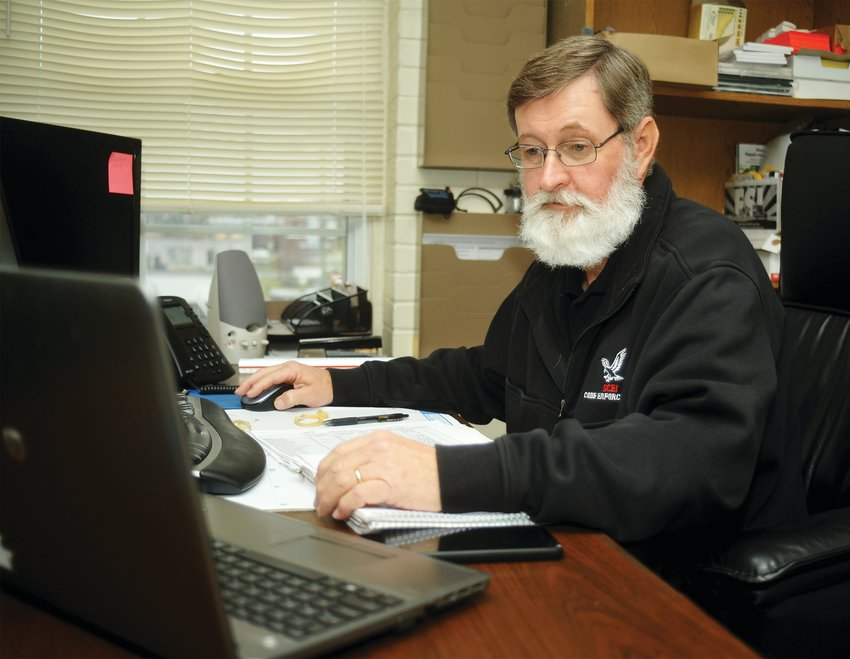 George McDuffie, who works with State Code Enforcement Inc., examines a list of recent code violations in Siler City. The town contracts with SCEI for its services.