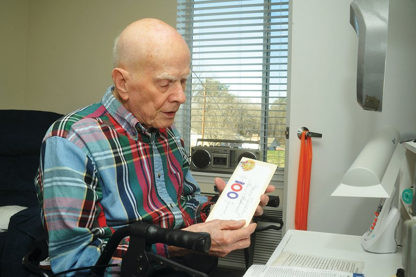 Laroy Stevenson sits at his desk with a congratulatory birthday card from Pittsboro Christian Village on the occasion of his 100th birthday. He is the facility's second-oldest resident, and has been in the home for 18 years.