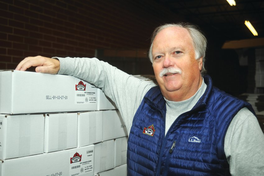 Jerry 'Twig' Wood III, president of Brookwood Farms in Siler City, stands with boxes of pork products that are ready for shipping. Wood is part of four generations of family members working at Brookwood Farms, which got its start in 1978.