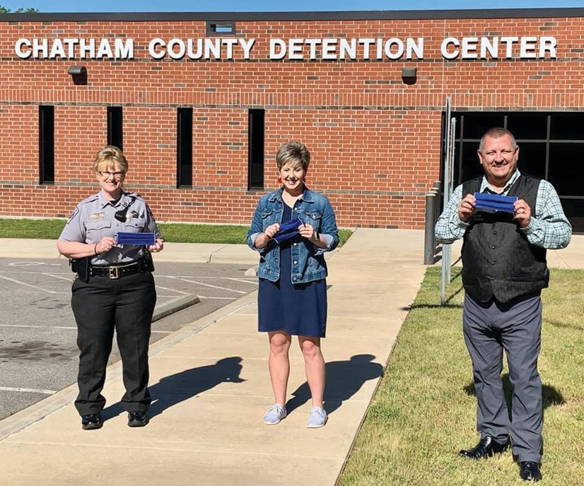 Chatham County Sheriff Mike Roberson poses with Tammy Kirkman and Jill Charville — and their face masks — outside Chatham's Detention Center.