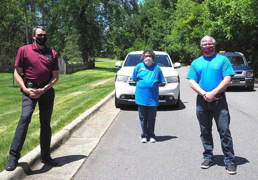 El Diputado Rocky Smith de la Oficina del Sheriff del Condado de Chatham, la Directora de Actividades de Cambridge Hills Angela de Muinck y el Director Ejecutivo Mike Walters ayudaron a facilitar el 'drive-by' del viernes en el asilo de ancianos de Pittsboro.