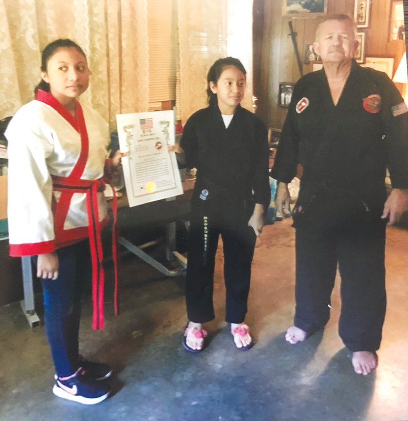 Ariely Santana, 10, of Siler City, officially recieved her black belt on May 20. Santana (middle) is pictured here with her cousin, Edna Santana, and her instructor, Larry Mabe.