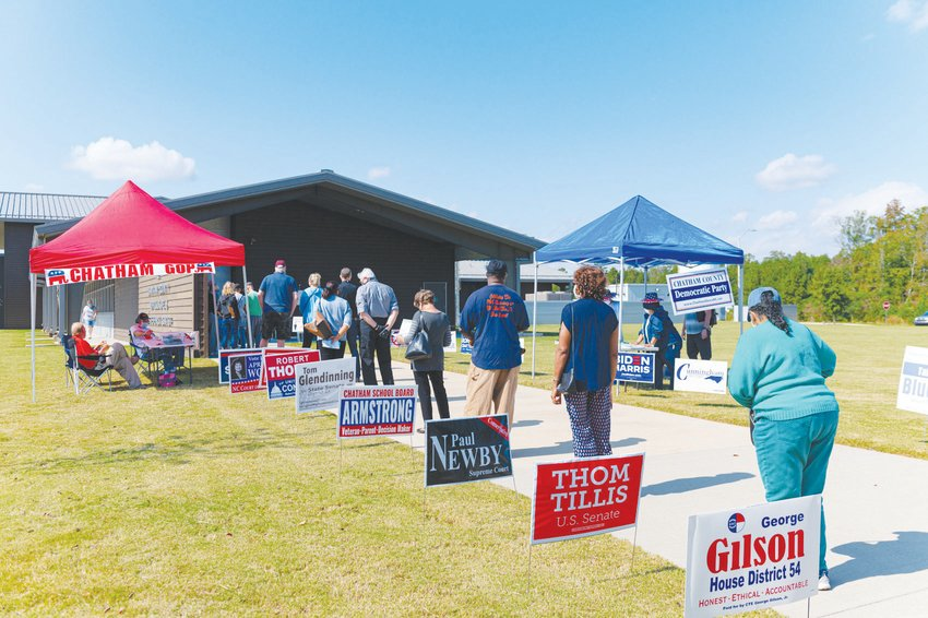 Pictured here on the first day of early voting, Chatham residents line up with six feet of distance between them to cast their ballots.