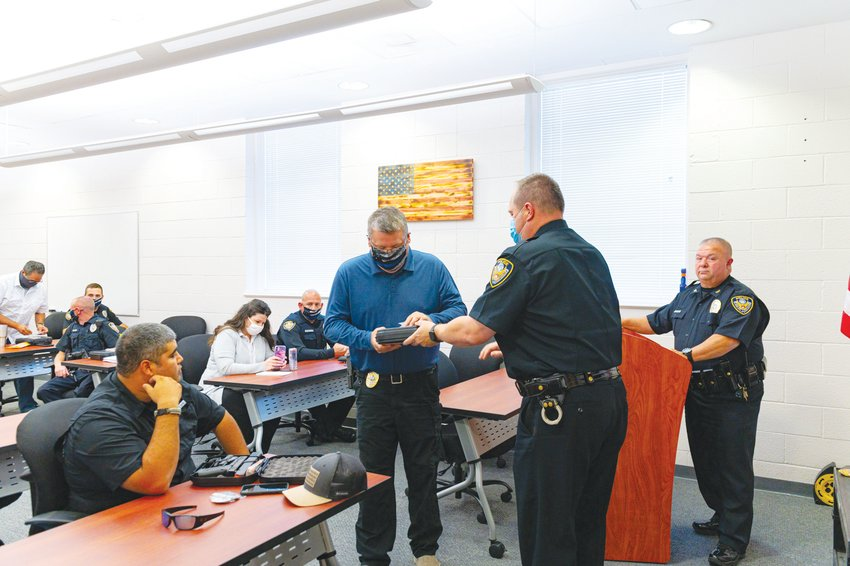 Siler City Chief of Police Chief Mike Wagner, right, watches as his officers accept their new badges last October. The department held a ceremony last Friday to officially recognize two new sergeants.