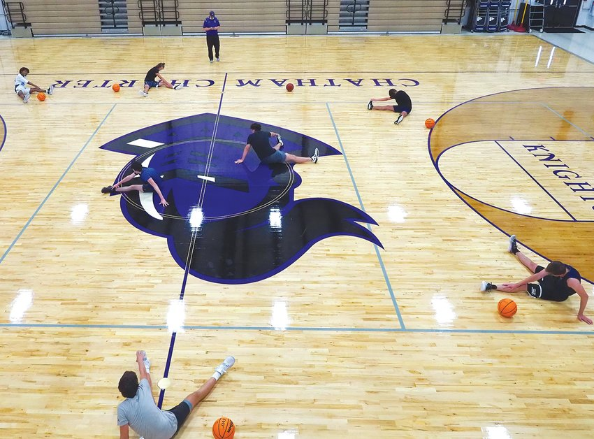 Chatham Charter men's basketball athletes stretch at a socially distanced workout on their Siler City campus in June.